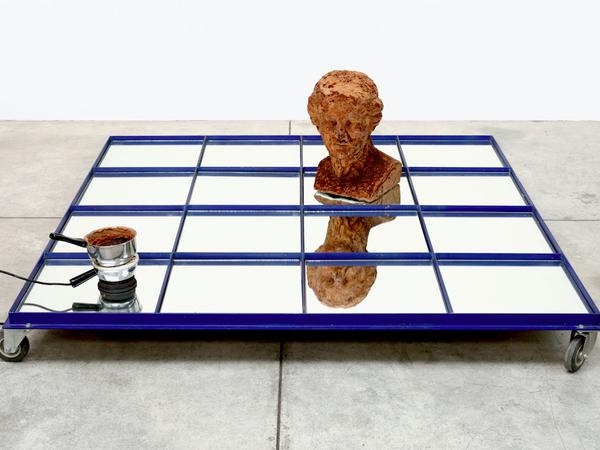 Vettor Pisani, Quadrato Magico, 2004. Metal frame, 16 mirror panels, chocolate. Venus, electric cooker, pan. 160 x 160 x 60 cm.