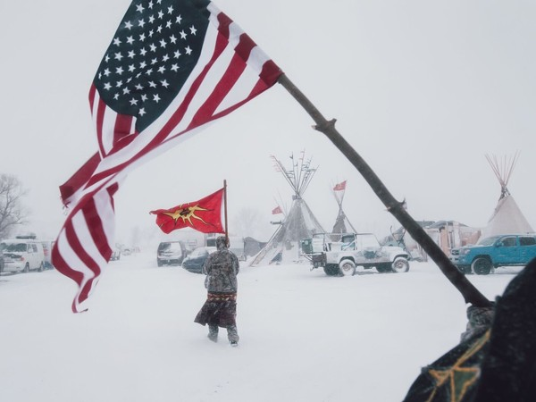 Contemporary Issues - First Prize, Stories © Amber Bracken, Standing Rock, Alcune persone portano la bandiera americana e quella della Mohawk Warrior Society al campo di protesta contro il Dakota Access Pipeline, in Cannon Ball, North Dakota, USA