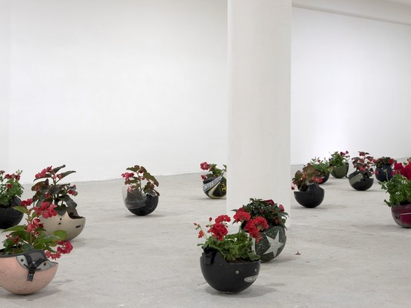 Sandro Mele, Piazza, 2017, caschi, terra, fiori rossi