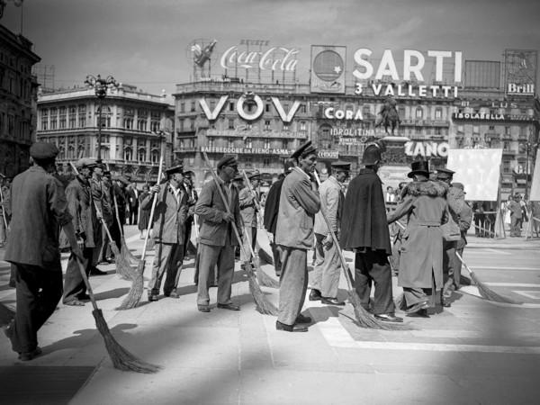 Comparse che interpretano degli spazzini fotografate in Piazza del Duomo durante la lavorazione di una scena del film Miracolo a Milano di Vittorio De Sica, 1951