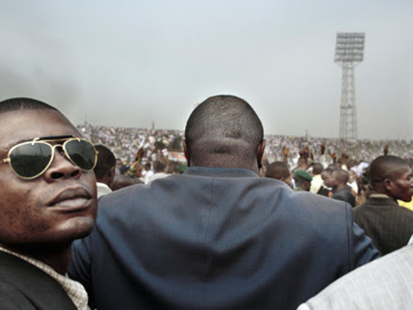 "Guy Tillim, Jean-Pierre Bemba surrounded by his body guards walks into an election rally in central Kinshasa, 2006, from the series ""Congo Democratic"""