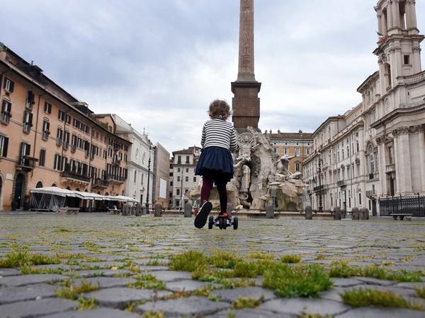 Roma, 18 aprile 2020. In una Piazza Navona deserta, con l'erba che cresce tra i sampietrini, una bambina corre in monopattino dopo la decisione del governo di permettere brevi uscite per fare esercizio fisico