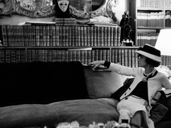 Douglas Kirkland, Ritratto di Gabrielle Chanel sul suo divano mentre guarda la sua biblioteca, Luglio 1962. Fotografia Collezione Douglas Kirkland, Los Angeles