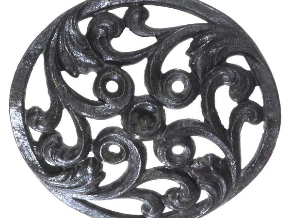 Placchetta circolare decorata con racemi, probabilmente fissata all'abito a scopo ornamentale con un rivetto ancora inserito in posizione centrale. Lega di rame, dal XIII secolo
