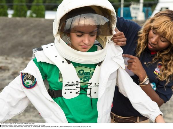 L'allenatrice di equipaggi Latina Rivers aiuta Amber, 16 anni, di Pittsburgh, a vestirsi per camminare su una superficie lunare simulata durante uno Space camp a Huntsville, Usa