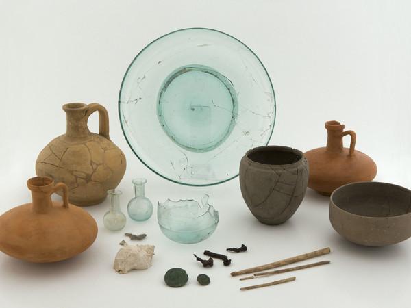 Via Spiné (2013), Tomba 13, Seconda metà Ι - inizi ΙΙ secolo d.C. Vari materiali:Olpe, bicchiere, coppe, piatto in vetro azzurro trasparente, balsamari,  spilloni, monete