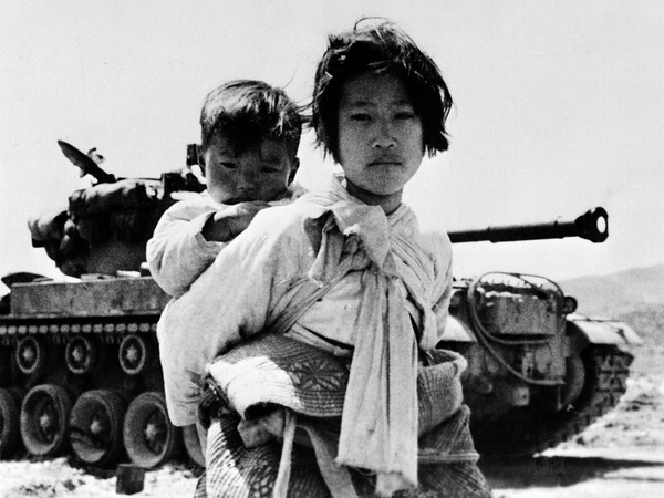 Ragazzina coreana con il fratello sulle spalle a nord di Seul durante la guerra di Corea, 1951